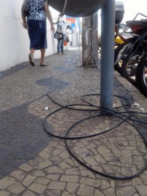 Fios caídos próximos a orelhão e poste na Avenida 4, Centro de Rio Claro