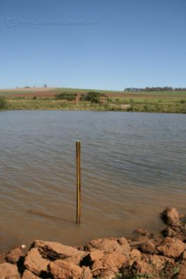 Em primeiro plano, medidor colocado às margens da lagoa