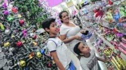 Hosana Nunes de Freitas e os filhos André (de pé) e Davi escolhem produtos de Natal em loja estabelecida na Rua 3, Centro