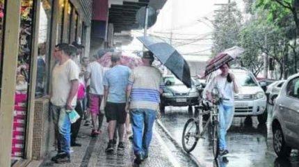 Os consumidores caminhavam sob chuva na Rua 4 na tarde dessa terça-feira (23). As lojas abrem hoje das 9 às 18 horas