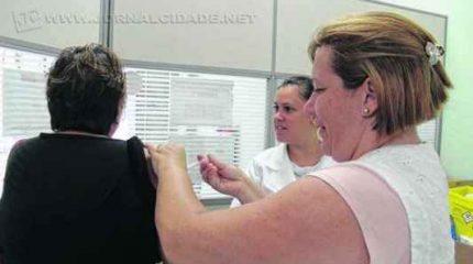 Mulher toma a vacina contra a gripe em posto extra montado na Farmácia Popular, região central da cidade