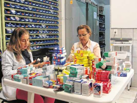 Voluntárias realizam a triagem dos medicamentos recebidos na farmácia do Abrigo; validade e condições são verificadas