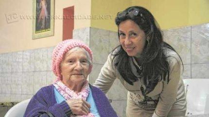 Voluntária ao lado de Dona Ambrosia, 96 anos de idade, que está no abrigo há 16 anos