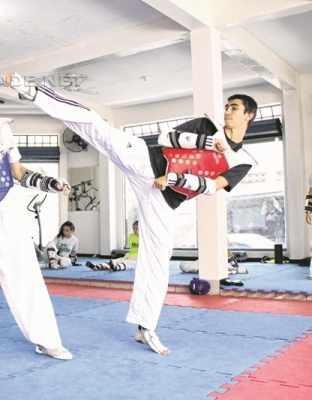 O atleta Guilherme Dias (à direita) durante treino na academia da equipe Carmen Carolina Pro Team de Taekwondo