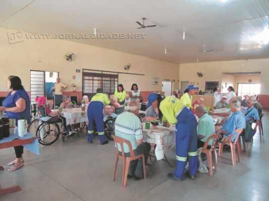 Moradores do Lar dos Velhinhos e funcionários da empresa Latina participam de café da tarde após entrega de cadeiras de rodas