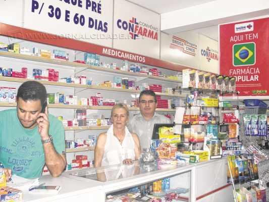 Denis Camargo, Cida e Paulo Cézar Carvalho Martinez no balcão da farmácia. Proprietária do estabelecimento fala sobre o fim do programa Farmácia Popular