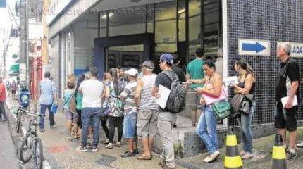 Uma imensa fila se formou na porta da agência da Caixa Econômica Federal na manhã dessa terça-feira (27), primeiro dia de atendimento após o fim da greve
