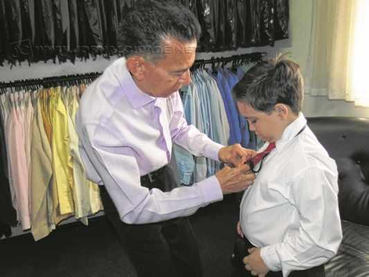 O pequeno Luis Henrique Grego Firmano, de 7 anos, recebe a ajuda de Augusto ao experimentar roupa para um casamento