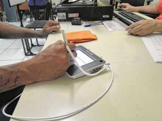 Eleitor faz assinatura digital durante atendimento para o cadastramento biométrico
