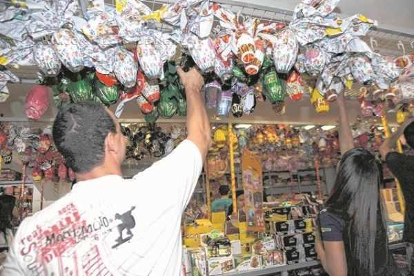 O cliente Joel Calderan é atendido pela vendedora Ana Paula Vilar na compra dos ovos para os filhos em loja de chocolates na região central de Rio Claro