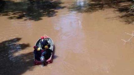 Corpo de Bombeiros trabalha com três homens na água e um barco durante as buscas pelo jovem